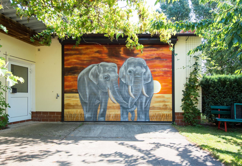 Garagentor Graffiti Berlin – Elefanten im Sonnenuntergang